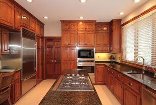 Traditional Kitchen with full backsplash, stone tile floors, Built In Refrigerator, U-shaped, Kitchen island, can lights