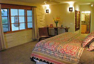 Mediterranean Master Bedroom with Ceiling fan, Wall sconce, flush light, Carpet