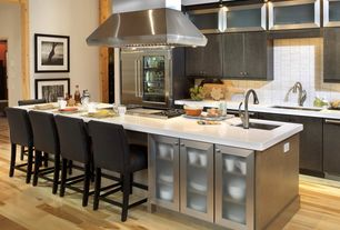 Contemporary Kitchen with can lights, High ceiling, Ceramic Tile, Corian counters, electric cooktop, Built In Refrigerator