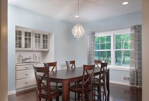 Traditional Dining Room with Hardwood floors, double-hung window, Pendant light, Standard height, Built-in bookshelf