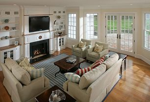 Traditional Living Room with Laminate floors, stone fireplace, Crown molding, Built-in bookshelf, French doors