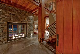 Craftsman Entryway with Oversize fireplace, Staircase with metal railing, Stained concrete floor, Loft, Barn door, Columns