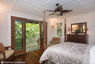 Tropical Master Bedroom with Hardwood floors, sliding glass door, Standard height, Ceiling fan, Wall sconce, Crown molding