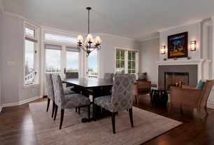Contemporary Dining Room with Hardwood floors, stone fireplace, Chandelier, Transom window, French doors, Crown molding