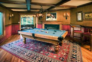 Country Game Room with Chandelier, Chair rail, Box ceiling, Wall sconce, stone fireplace, Hardwood floors, Exposed beam