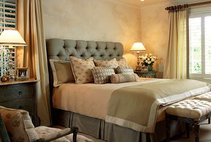 Traditional Master Bedroom with Upholstered armchair, Carpet, Tufted stools, Crown molding, Nightstand, Painted wood blinds