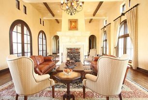 Mediterranean Living Room with Exposed beam, Hardwood floors, French doors, Arched window, Chandelier