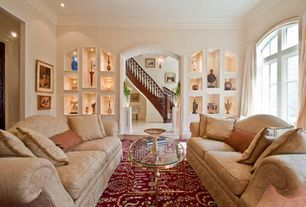 Traditional Living Room with Standard height, Crown molding, Arched window, Casement, Built-in bookshelf, can lights, Carpet
