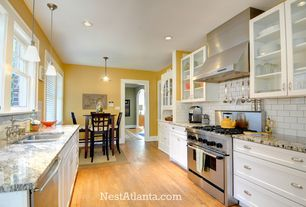 Traditional Kitchen with Complex granite counters, Giallo Napoleone, built-in microwave, gas range, Glass Front Doors, Flush