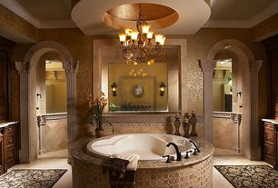 Mediterranean Master Bathroom with Wall sconce, Crown molding, drop in bathtub, Standard height, Wrought iron chandelier