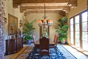 Rustic Dining Room with limestone floors, Chandelier, Wall sconce, Standard height, French doors, Exposed beam