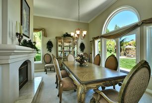 Traditional Dining Room with Crown molding, insert fireplace, Cement fireplace, picture window, Standard height, Chandelier