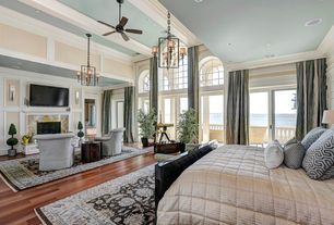 Traditional Master Bedroom with Natural light, Hardwood flooring, Ceiling fan, Arched window, High ceiling