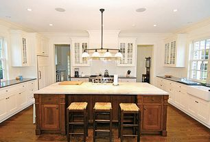 Country Kitchen with Crown molding, Stone Tile, can lights, Farmhouse sink, Kitchen island, European Cabinets, Custom hood