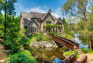 Country Exterior of Home with Gravel driveway, Trellis, Wood bridge, River rock exterior facade, Pond
