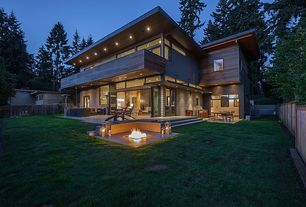 Contemporary Exterior of Home with folding door, Outdoor kitchen, Fire pit, Deck Railing, picture window, Fence