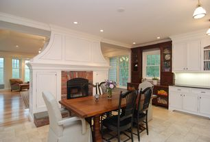 Traditional Dining Room with Crown molding, flush light, metal fireplace, limestone floors, Built-in bookshelf