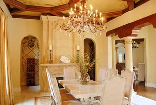 Mediterranean Dining Room with High ceiling, Crown molding, Concrete floors, Exposed beam, Cement fireplace, Chandelier