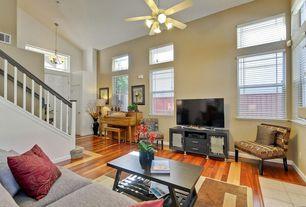 Contemporary Living Room with Chandelier, six panel door, picture window, High ceiling, Ceiling fan, Hardwood floors