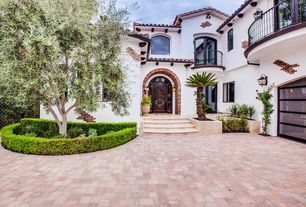 Mediterranean Front of Home with Barn door, exterior brick floors, Raised beds, Transom window, Pathway, French doors