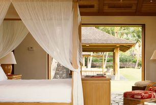 Tropical Guest Bedroom with limestone floors, Built-in bookshelf