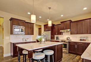 Craftsman Kitchen with Wood island legs, European Cabinets, Wall Hood, Paint, Subway Tile, Flat panel cabinets, Flush