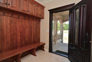 Craftsman Mud Room with Built-in bookshelf, travertine tile floors, Crown molding, Glass panel door
