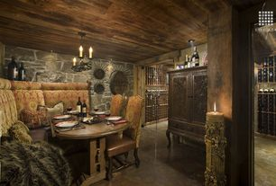 Eclectic Wine Cellar with Chandelier, Concrete floors, Natural stone wall, Columns