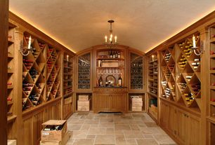 Traditional Wine Cellar with Chandelier, limestone tile floors, Built-in bookshelf, Wall sconce