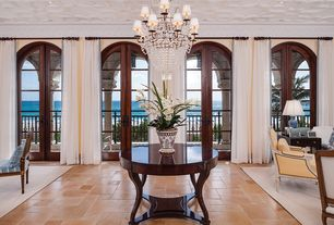 Mediterranean Entryway with Chandelier, French doors, limestone floors, Crown molding