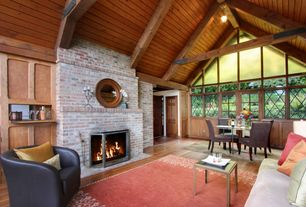 Craftsman Living Room with brick fireplace, Cathedral ceiling, picture window, Exposed beam, interior brick, French doors