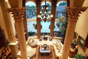 Mediterranean Entryway with sandstone tile floors, Cement fireplace, Chandelier, Arched window, stone tile floors, Columns
