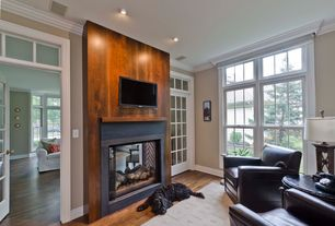 Modern Living Room with Glass panel door, Double sided fireplace, Hardwood floors, Transom window, Crown molding