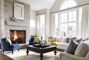 Traditional Living Room with Trexus intro tub reception chair, High ceiling, Arched window, Hardwood floors, stone fireplace
