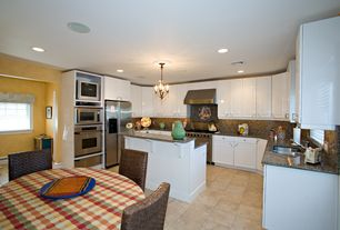 Cottage Kitchen with Simple granite counters, Raised panel, Flush, Kitchen island, Pendant light, limestone tile floors