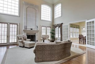 Traditional Living Room with Arched window, French doors, Hardwood floors, High ceiling