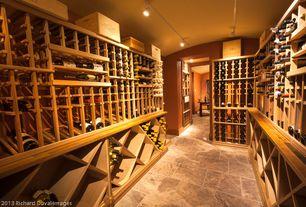 Craftsman Wine Cellar with Built-in bookshelf, sandstone floors, flush light