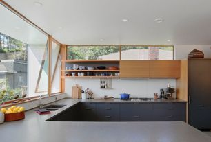 Modern Kitchen with wall oven, Solid surface countertop, European Cabinets, Paint 1, picture window, U-shaped, can lights