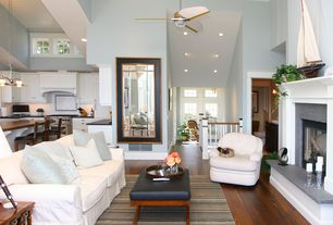 Cottage Living Room with specialty door, High ceiling, Hardwood floors, flush light, Ceiling fan, Paint, Cement fireplace