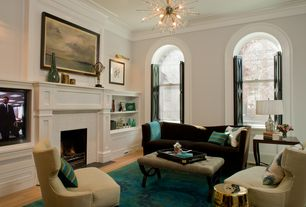 Traditional Living Room with Hardwood floors, Chandelier, Cement fireplace, Crown molding, Built-in bookshelf, Arched window