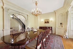 Traditional Dining Room with Hardwood floors, double-hung window, Chandelier, Standard height, Wall sconce, Crown molding