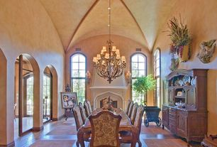 Mediterranean Dining Room with High ceiling, terracotta tile floors, Arched window, Built-in bookshelf, Chandelier, Columns