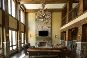 Rustic Living Room with Chandelier, Columns, Hardwood floors, stone fireplace, Cathedral ceiling, Exposed beam, Loft