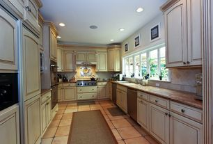 Traditional Kitchen with U-shaped, two dishwashers, Custom hood, Simple granite counters, Raised panel, Stone Tile