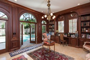 Traditional Home Office with Built-in bookshelf, Chair rail, Crown molding, sandstone tile floors, Arched window, Chandelier