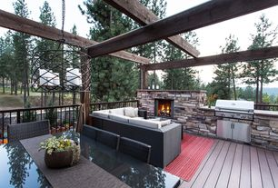 Rustic Deck with Outdoor fireplace, Outdoor seating/dining, Fence, Outdoor wicker sectional sofa, Outdoor rug, Exposed beams