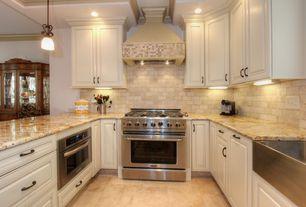 Traditional Kitchen with limestone tile floors, U-shaped, Farmhouse sink, Breakfast bar, Custom hood, Stone Tile