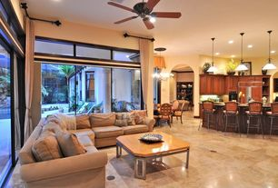 Traditional Great Room with sliding glass door, stone tile floors, High ceiling, Pendant light, Chandelier, Transom window