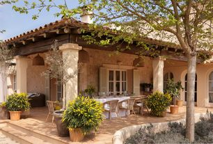 Mediterranean Porch with Arched window, Palmetto All-Weather Wicker Stacking Armchair - Honey, exterior stone floors