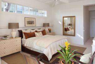 Tropical Guest Bedroom with Standard height, Ceiling fan, Built-in bookshelf, flat door, picture window, can lights, Carpet